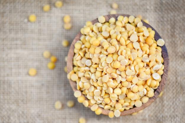 袋の背景に木製ボウル農産物の大豆-皮のない皮をむいた分割大豆または大豆