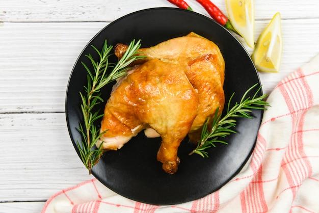 ローストチキンローズマリー-焼き鶏の脚焼きバーベキュー休日のダイニングテーブルでおいしい食べ物を祝う、トップビュー