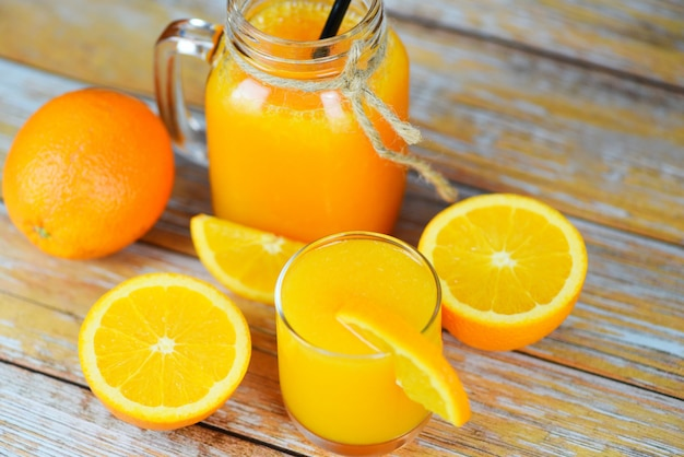 ガラスの瓶にオレンジジュースと木製のテーブルに新鮮なオレンジフルーツスライス-木材の背景に静物ガラスジュース