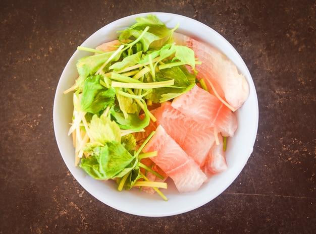 セロリでスライスした新鮮な魚の切り身-白いボウルに生ティラピアの切り身魚