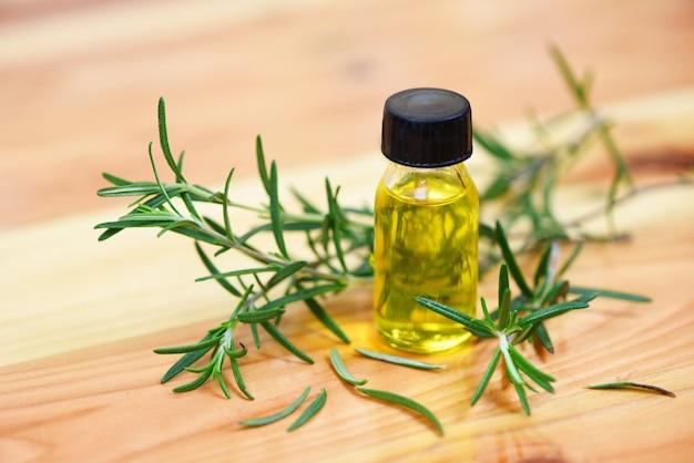 Бутылка эфирного масла натуральные ингредиенты спа-масла розмарина для ароматерапии и листьев розмарина на фоне дерева - органическая косметика с экстрактами трав
