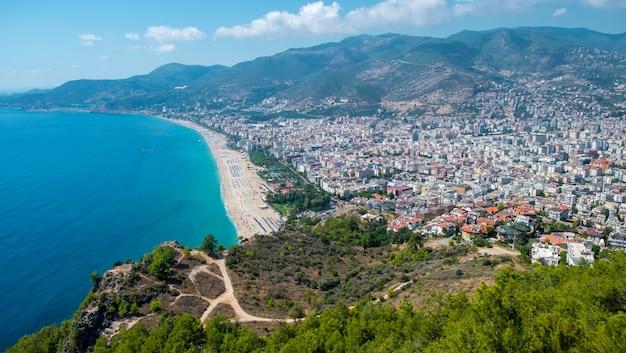 青い海と港都市背景-美しいクレオパトラビーチアラニヤトルコ風景旅行ランドマークの海岸と山のアラニヤビーチトップビュー