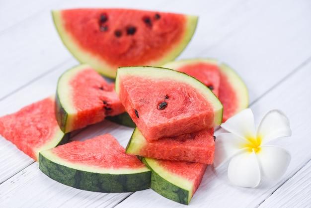 Фон ломтик свежего арбуза / летний фрукт арбуз и белый цветок