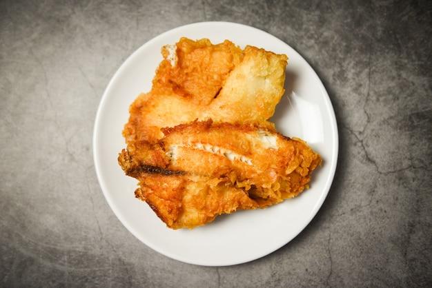 揚げ魚の切り身をステーキやサラダ料理、トップビューコピースペース-ティラピアの切り身魚クリスピー白いプレートで提供しています