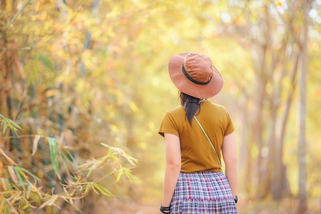 秋のファッションコンセプト-アジアの女の子の散歩と公園の背景、日本の帽子をかぶっている若い女性で秋の木の森に立って