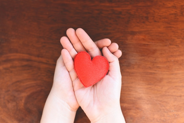 Женщина держит красное сердце на руках