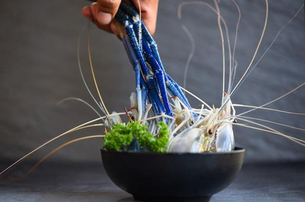 シーフードレストランで暗い背景にトムヤムクンタイ料理を調理するためのレモングリーンパセリのスパイスと新鮮なエビ-ボウルに生えび
