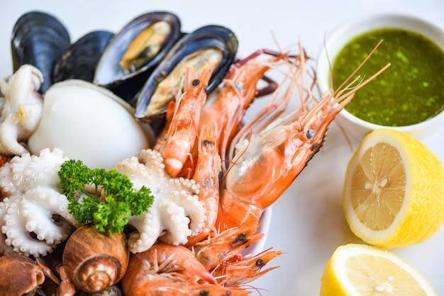 新鮮なエビエビイカムール貝は白いプレートの背景にバビロン貝カニとシーフードソースレモンを発見-調理された汽船料理シーフードビュッフェコンセプト