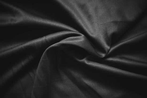 抽象的な暗い黒しわ生地テクスチャ背景-滑らかでエレガントな黒絹、サテンの高級布波