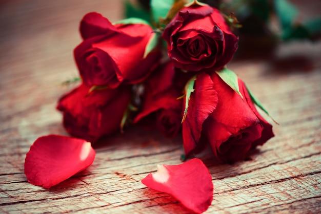 花は花びらのロマンチックな愛のバレンタインの日の概念を上昇しました。素朴な木の上の赤いバラの花の花束