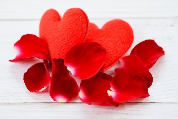 Лепестки роз и сердце на белом деревянном