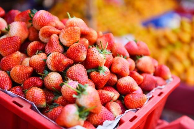 市場の果物の販売のためのバスケットで熟したイチゴの山