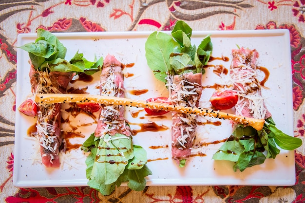 Салат из говядины. мясо говяжий рулет свежие овощи с соусом в ресторане турецкие блюда в турции