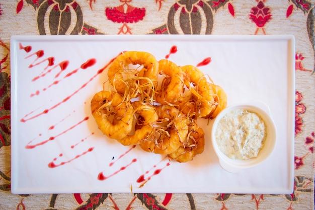 Кольца кальмаров, обжаренные на белой тарелке с соусом. ресторан турецкой кухни в турции