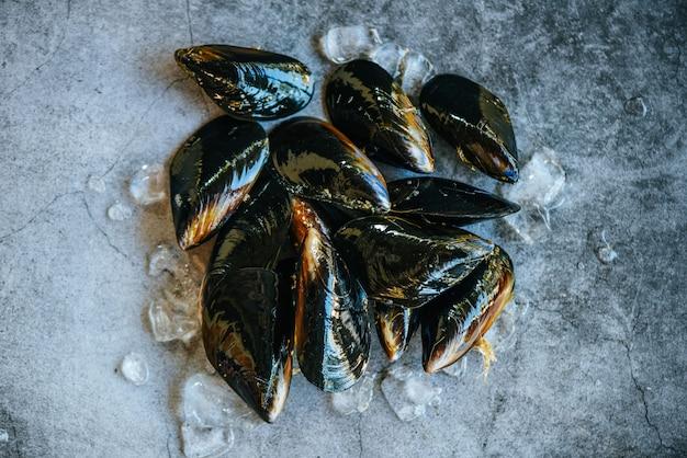 レストランまたは市場で販売されているムール貝の殻付きの新鮮な魚介類。生のムール貝の氷と暗いプレート