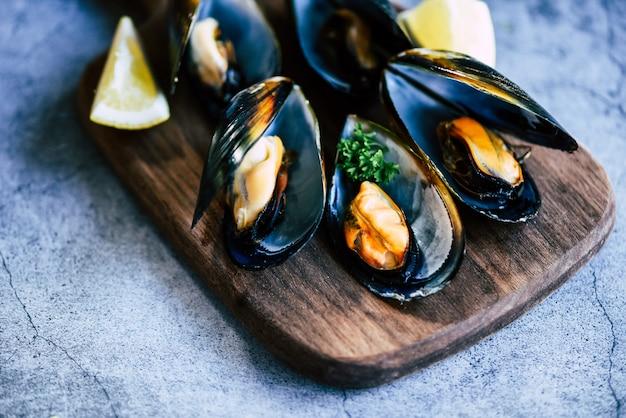 Приготовленные мидии с зеленью лимона и темной тарелкой. свежие морепродукты моллюсков на деревянной разделочной доске в ресторане мидии оболочки пищи