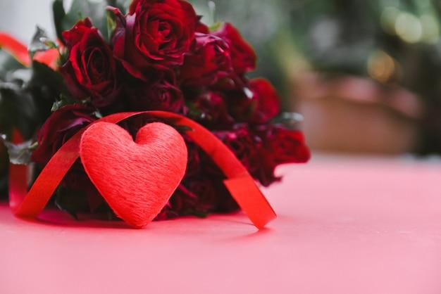 赤の花のバラの花束。リボンとバラのロマンチックな愛バレンタインの日の概念と赤いハート