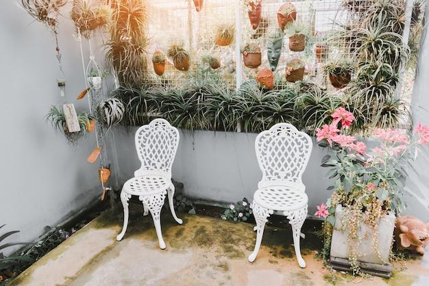 屋内温室環境のホームガーデニングとデコレーション秘密の庭とモダンなガーデニングは、ヴィンテージの椅子とライブウォールのあるワークスペースに花と植物と緑を設定します