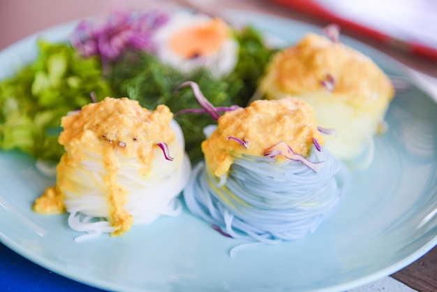 タイ料理のおいしくて美しい食べ物。カラフルなライスヌードルまたはタイライス春雨麺と魚カニのカレースープソースと野菜のプレート木製テーブル