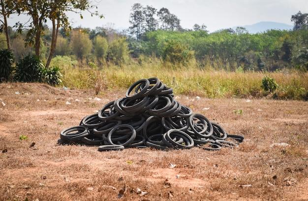 草の上の古いタイヤ。廃タイヤとゴムタイヤの処理のための産業埋立地ゴムリサイクル用の古いタイヤとホイールの山タイヤダンプ