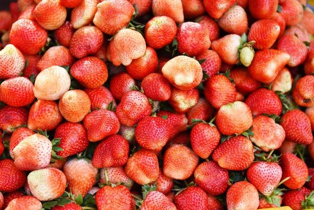 市場の果物の販売のための熟したイチゴの山。収穫された新鮮なイチゴ
