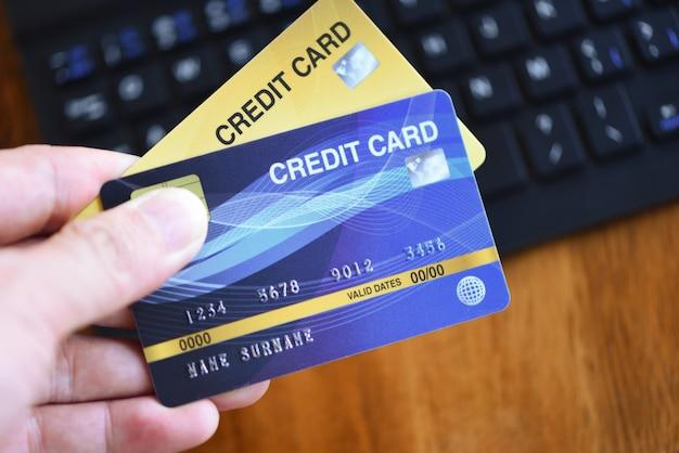 ビジネスの男の手はクレジットカードを保持し、オフィスのテーブルキーボードでオンラインショッピングにラップトップを使用して