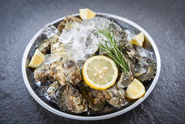 Свежие устрицы из морепродуктов на тарелку черный. раковина устриц с пряными травами лимон розмарин подается стол и лед здоровые морепродукты сырой устричный ужин в ресторане для гурманов