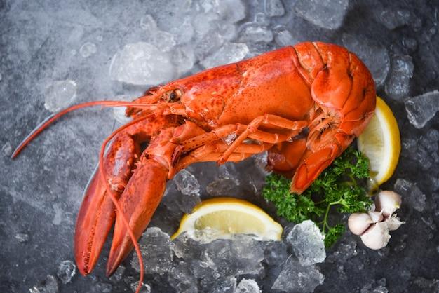Свежая еда омара на черной плите. красный обед из омаров морепродукты со специями из трав лимонный розмарин подается стол и лед в ресторане изысканная еда здоровый вареный омар приготовленный
