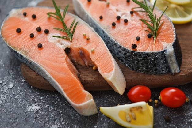 Сырое филе лосося и лед для приготовленного на гриле стейка из морепродуктов - свежий стейк из лосося с зеленью и специями, лимон розмарин, помидор на фоне деревянной разделочной доски