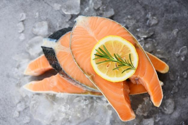 Крупным планом сырого лосося филе рыбы и льда - свежий сырой стейк из лосося с розмарином травы на черном фоне пластины