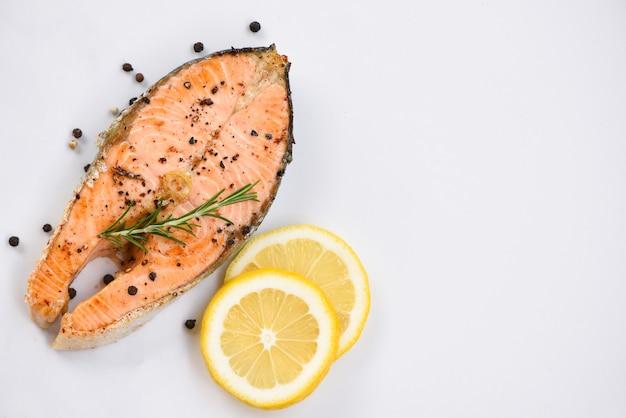Стейк из лосося на гриле с зеленью и специями лимон розмарин на тарелку фон крупным планом приготовленные филе лосося рыба стейк из морепродуктов