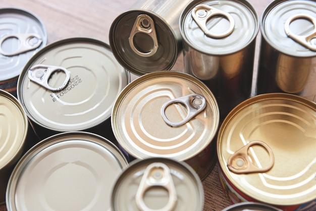 Различные консервы в металлических банках на деревянных, вид сверху - консервы не скоропортящиеся продукты для хранения продуктов на кухне дома или для пожертвований