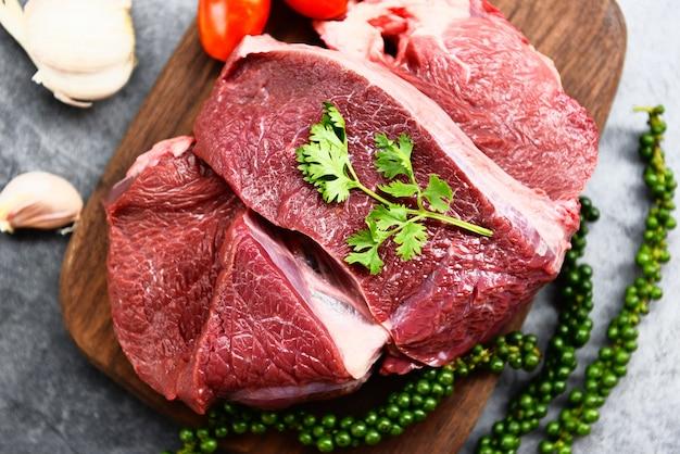 牛肉のステーキをローストまたは食材のハーブとスパイスで焼いたものを調理するためのキッチンテーブルの上の木製のまな板に生の牛肉