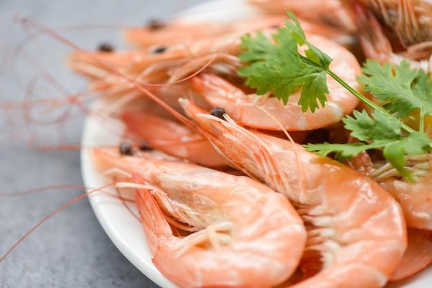 食材ハーブコリアンダー-食品のテーブル背景に料理海老エビの料理と白い皿に新鮮なエビ