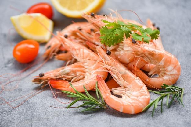食材ハーブとスパイスの暗い皿に新鮮なエビ-テーブルの背景に料理海老エビを調理