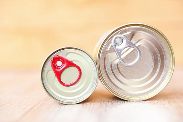 Консервы в металлических банках на деревянном фоне консервы не скоропортящиеся продукты для хранения продуктов на кухне дома или на пожертвования