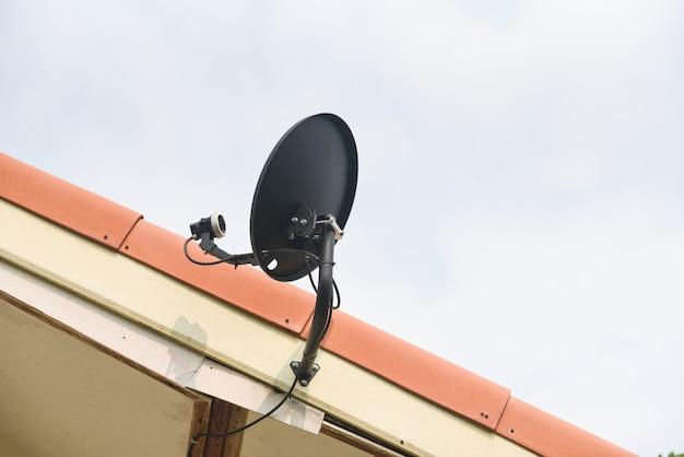 家の屋根の衛星放送パラボラテレビアンテナ-ディッシュコミュニケーション