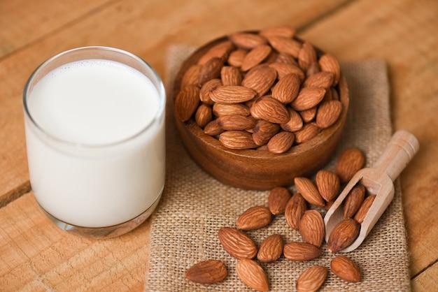 Миндальное молочное стекло на завтрак здоровая пища - миндальные орехи на деревянной стене чаши