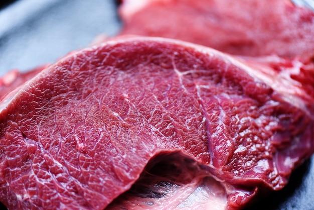 Закройте вверх предпосылки текстуры мяса говядины деталей сырцовой. свежий говяжий ломтик животного белка