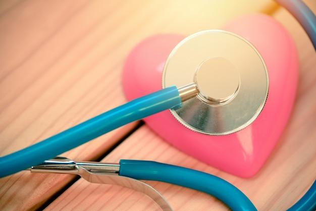 心臓の健康と聴診器の世界のハートの日世界の健康の日または世界の高血圧の日と健康保険の概念と赤いハート