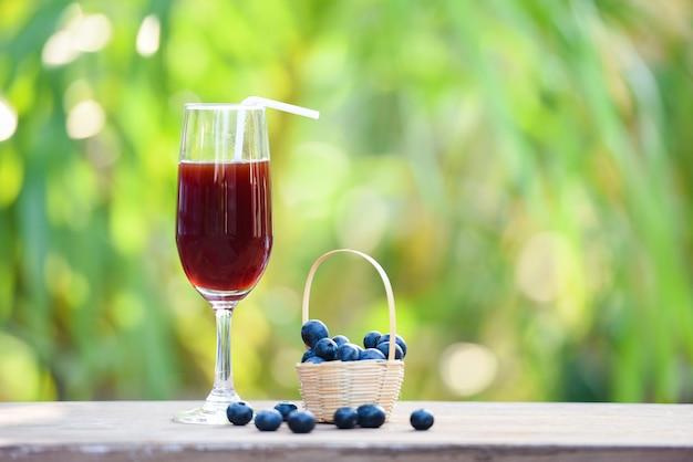 ブルーベリーのスムージージュースガラスと新鮮なブルーベリーの果実、自然の緑の夏の背景付きバスケット