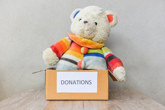テディベア人形の木製のテーブル背景を持つ寄付ボックス