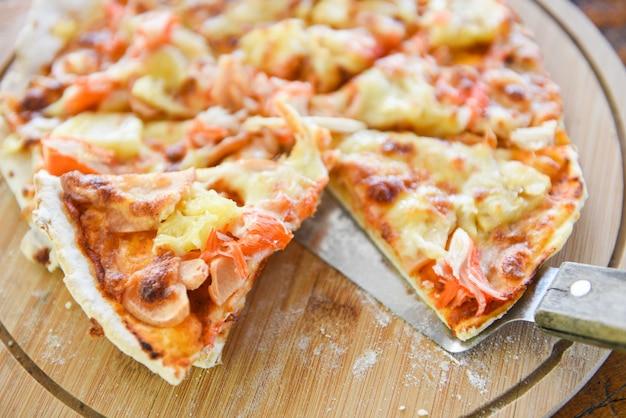 木製トレイのピザチーズスライスと木製のテーブルで提供しています