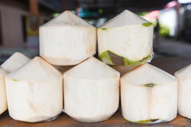 木製のテーブルのクローズアップに新鮮なココナッツ