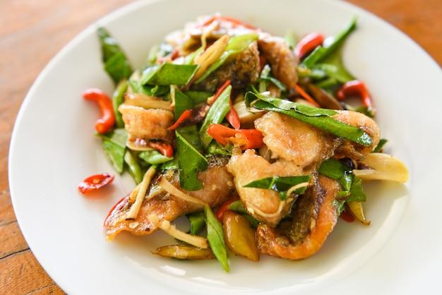 タイ料理は、白い皿に唐辛子唐辛子と魚のフライを炒め