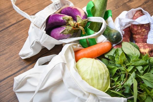 Свежие овощи органические в эко-хлопчатобумажных мешках на деревянном столе
