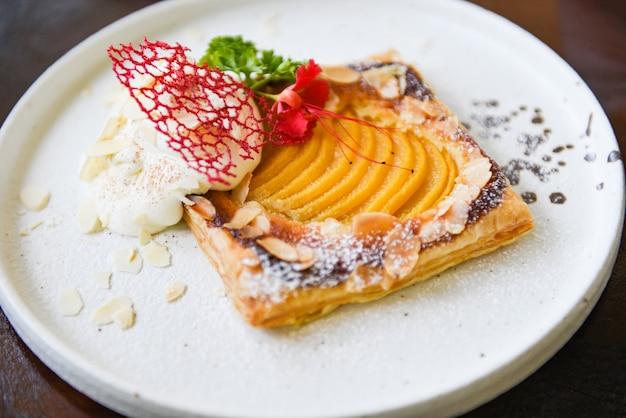 白いプレートのクローズアップの桃のパイ