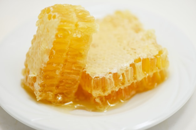 新鮮な蜂蜜/プレート自然健康食品に黄色の甘いハニカムスライスのクローズアップ