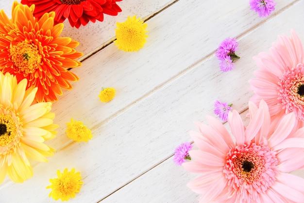Свежие весенние цветы герберы разноцветные и цветочные различные на деревянный стол