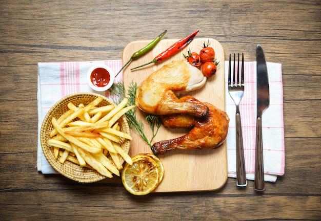 フライドポテトバスケットケチャップトマトレモン唐辛子とプレート木の板に鶏のグリル足